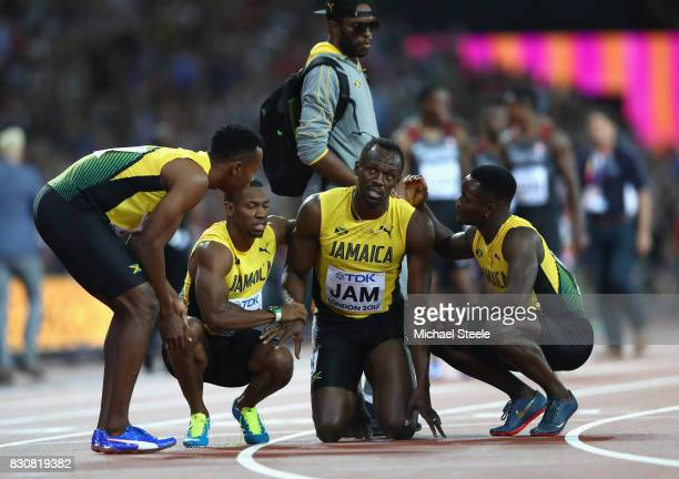 Usain Bolt of Jamaica is helped up by teammmates Yohan Blake Julian Forte and Omar McLeod after falling in the Men's 4x100 Relay final during day...