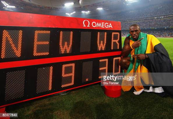 Usain Bolt of Jamaica poses next to the clock after breaking the world record with a time of 1930 seconds to win the gold medal in the Men's 200m...