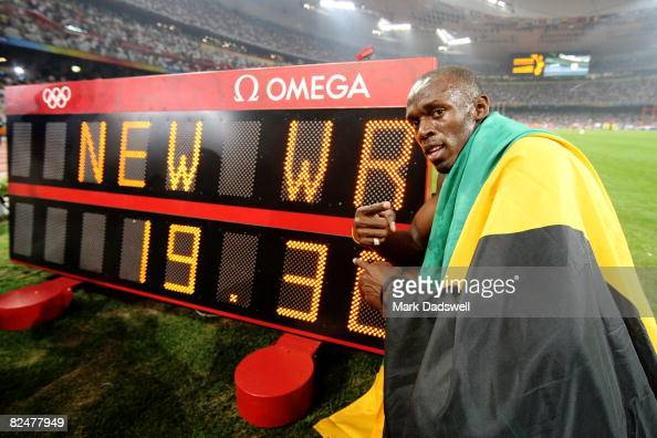 Usain Bolt of Jamaica poses next to the clock after breaking the world record with a time of 1930 to win the gold medal in the Men's 200m Final at...