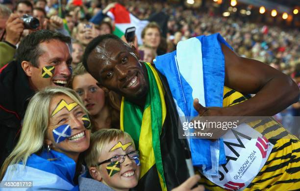 Usain Bolt of Jamaica poses with fans as he celebrates winning gold in the Men's 4x100 metres relay final at Hampden Park during day ten of the...