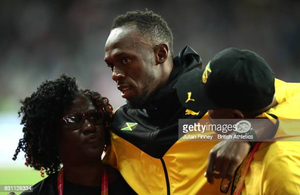 Usain Bolt of Jamaica poses with his parents as he bids farewell after his last World Athletics Championships during day ten of the 16th IAAF World...