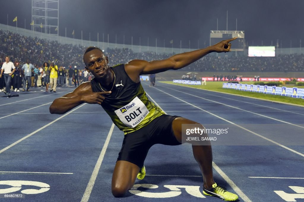 TOPSHOT - Usain Bolt (C) of Jamaica reacts after winning his final race in home country during the Racers Grand Prix at the national stadium in Kingston, Jamaica, on June 10, 2017. Bolt partied with his devoted fans in an emotional farewell at the National Stadium on June 10 as he ran his final race on Jamaican soil. Bolt is retiring in August following the London World Championships. / AFP PHOTO / Jewel SAMAD