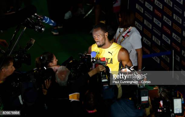 Usain Bolt of Jamaica reacts while giving media interviews after winning Heat 6 of Round 1 of the Men's 100 Metres during day one of the 16th IAAF...