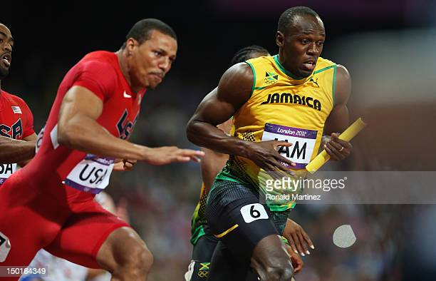 Usain Bolt of Jamaica receives the relay baton from Yohan Blake of Jamaica next to Ryan Bailey of the United States during the Men's 4 x 100m Relay...