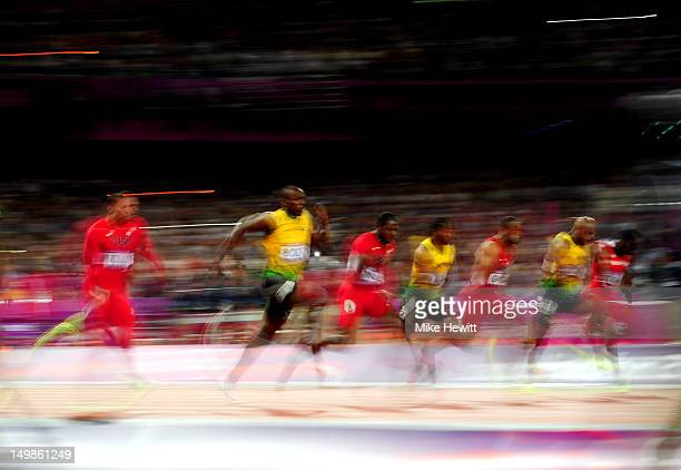 Usain Bolt of Jamaica runs ahead of Yohan Blake of Jamaica and Justin Gatlin of the United States to win the Men's 100m Final on Day 9 of the London...