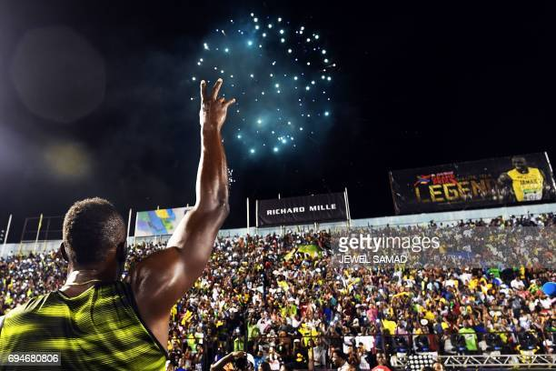 TOPSHOT Usain Bolt of Jamaica salutes the crowd after running his final race in home country during the Racers Grand Prix at the national stadium in...