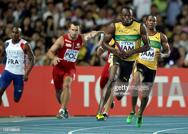 Usain Bolt of Jamaica takes the baton from Yohan Blake as he sprints to victory and a new world record in the men's 4x100 metres relay final during...