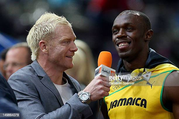 Usain Bolt of Jamaica talks with Former Olympian Iwan Thomas after winning the gold medal in the Men's 100m Final on Day 9 of the London 2012 Olympic...