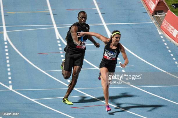 Usain Bolt top passes the battern to Jeneba Tarmob of the Bolt All Stars during the 4x100m mixed really at Lakeside Stadium on February 11 2017 in...