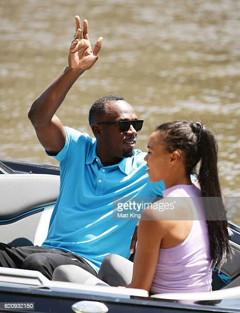 Usain Bolt waves to onlookers as he travels by boat with Australian Olympian Morgan Mitchell to the launch of Nitro Athletics on November 4 2016 in...