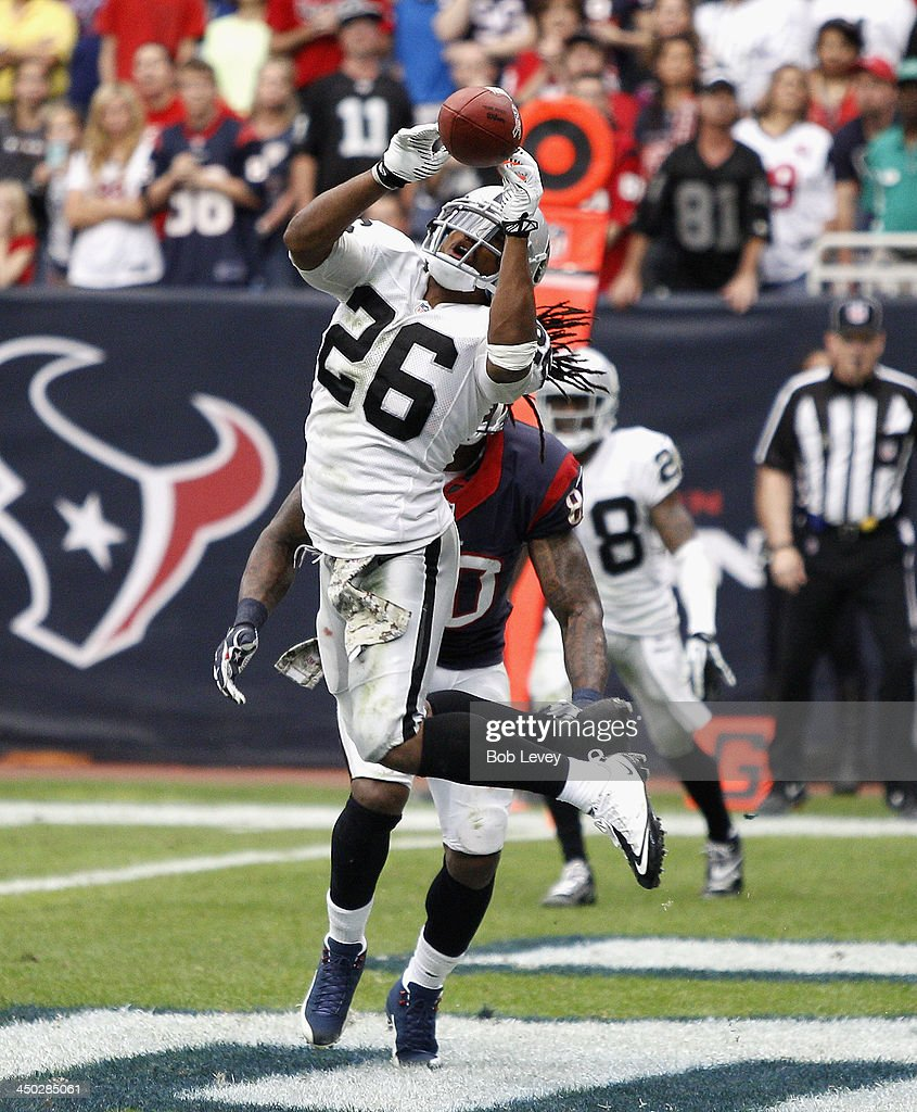 <a gi-track='captionPersonalityLinkClicked' href=/galleries/search?phrase=Usama+Young&family=editorial&specificpeople=4401869 ng-click='$event.stopPropagation()'>Usama Young</a> #26 of the Oakland Raiders has the ball just go off his fingertips as he jumps the route run by Andre Johnson #80 of the Houston Texans in the fourth quarter at Reliant Stadium on November 17, 2013 in Houston, Texas.