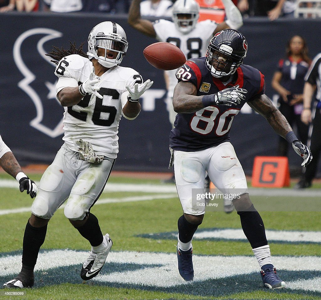 Usama Young #26 of the Oakland Raiders has the ball just go off his fingertips as he jumps the route run by Andre Johnson #80 of the Houston Texans in the fourth quarter at Reliant Stadium on November 17, 2013 in Houston, Texas.