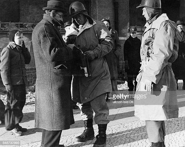 USAmerican soldiers search visitors of a black market in Berlin in February 1947