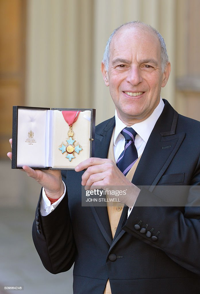 US-British television presenter Loyd Grossman poses with his medal after being appointed a Commander of the Order of the British Empire (CBE) for services to heritage at an investiture ceremony at Buckingham Palace in London on February 11, 2016. / AFP / POOL / John Stillwell