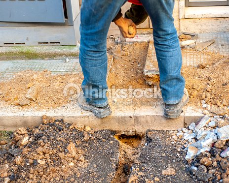 Use Pickaxe And Shovel To Dig Trench Stock Photo - Thinkstock