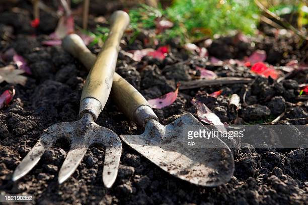A used hand ho and shovel in dirt