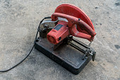 Used Portable Fiber Cut-off Machine in red and black colors on concrete floor for industry work