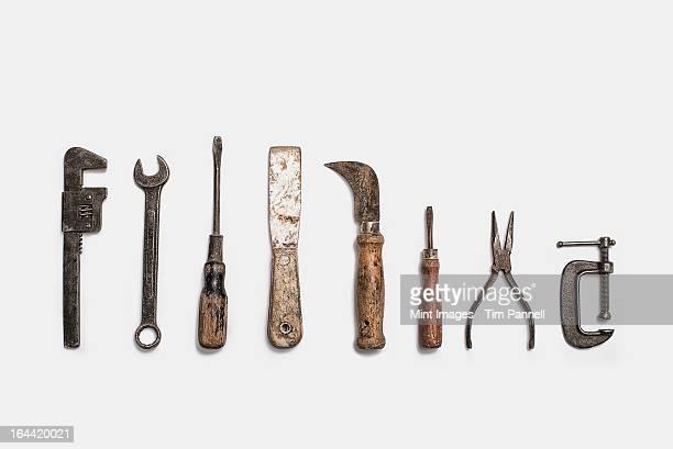 Used tools arranged in a row. Well used, worn handles, shaped wooden smooth texture. Metal rusty and marked implements.