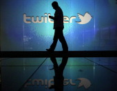 A user checks a Twitter feed on a smartphone in this arranged photograph taken in London UK on Friday Oct 4 2013 Twitter Inc's initial public...