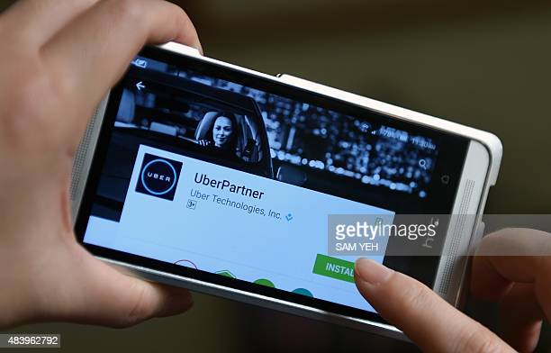 A user checks the Uber APP from a cellphone in Taipei on august 14 2015 Taiwan has fined Uber a total of 1 million USD since September for improper...