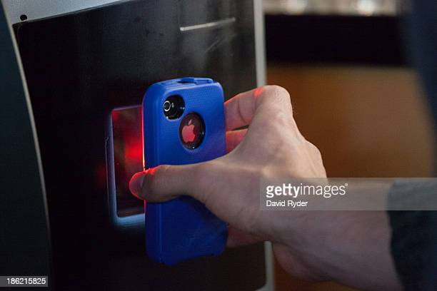 A user scans a QR code on their smart phone allowing bitcoins to be transferred into their digital wallet while using the world's first bitcoin ATM...