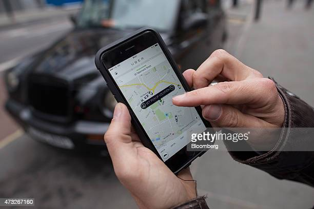 A user scans for an available vehicle using the Uber Technologies Inc's app on an Apple Inc iPhone 6 smartphone in this arranged photograph in London...