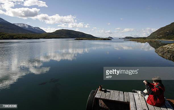 A tourist sits on March 31st on a wharf of the Lapataia bay where national route ends some 17848 kilometres from Alaska and 3063 from Buenos Aires in...