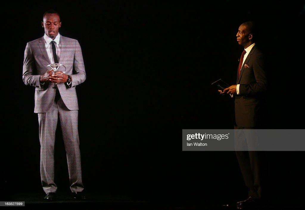 Usian Bolt talks to Laureus Academy Member <a gi-track='captionPersonalityLinkClicked' href=/galleries/search?phrase=Michael+Johnson+-+Leichtathlet&family=editorial&specificpeople=4208304 ng-click='$event.stopPropagation()'>Michael Johnson</a> as he accepts his award for 'Laureus World Sportsman of the Year' via video link during the awards show for the 2013 Laureus World Sports Awards at the Theatro Municipal Do Rio de Janeiro on March 11, 2013 in Rio de Janeiro, Brazil.