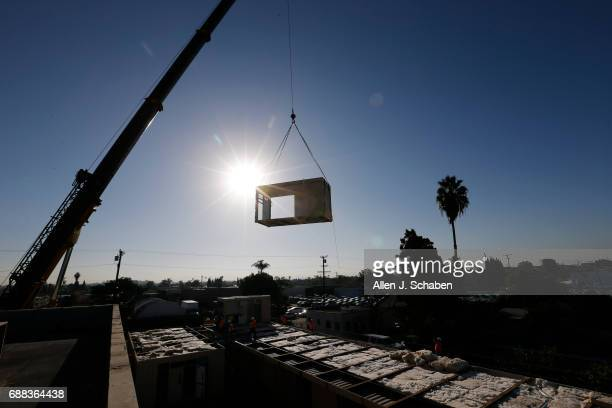 Using a crane construction workers position one of the twostory high preconstructed shipping containers that are being converted into housing for...