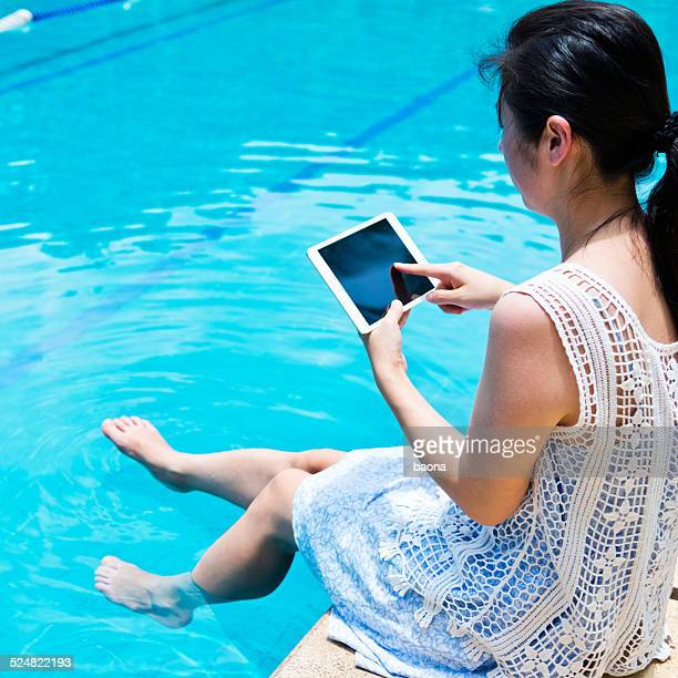 using a digital tablet by the pool