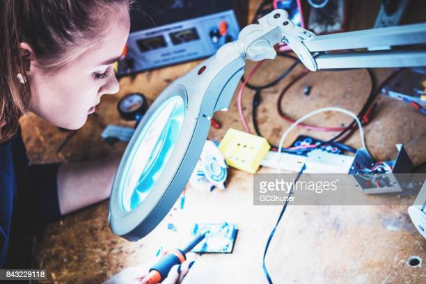 Using a lighted magnifier to precisely solder a circuit board.