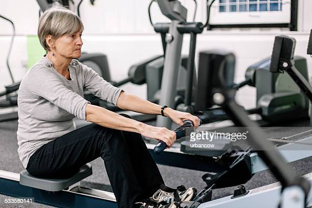 Using a rowing machine, senior woman in the gym