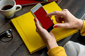 Woman using smart phone on the table with colorful books. Phone with empty screen for your application