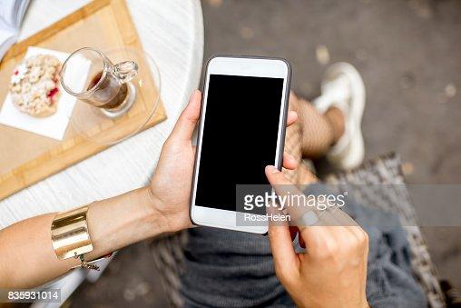 À l'aide d'un smartphone au café : Photo