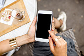 Woman holding a smart phone with empty screen sitting outdoors at the cafe with cake and coffee on the table