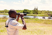 African Man at a safari park in Rwanda using binoculars to watch hippos