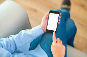 Hand holding a blank white screen smart phone on a couch.
