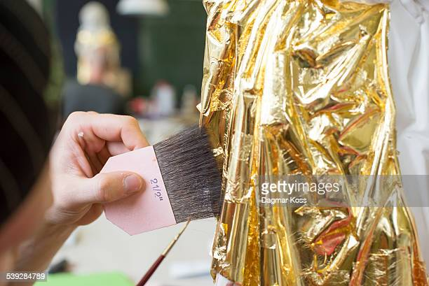 Using brush to apply leaf gold onto statue