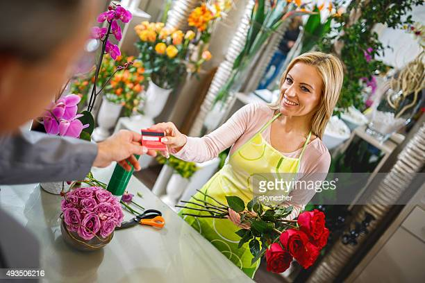Using credit card and buying roses in flower shop.