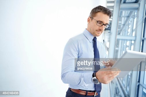 Using his tablet for corporate affairs : Stock Photo