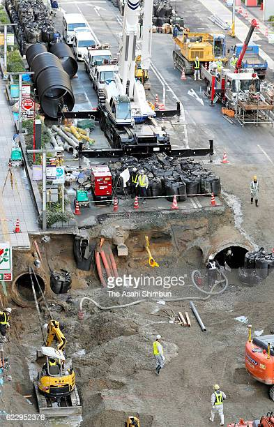 Using hydraulic cranes and power shovels construction workers fill in the sinkhole on November 11 2016 in Fukuoka Japan Efforts are now being made to...