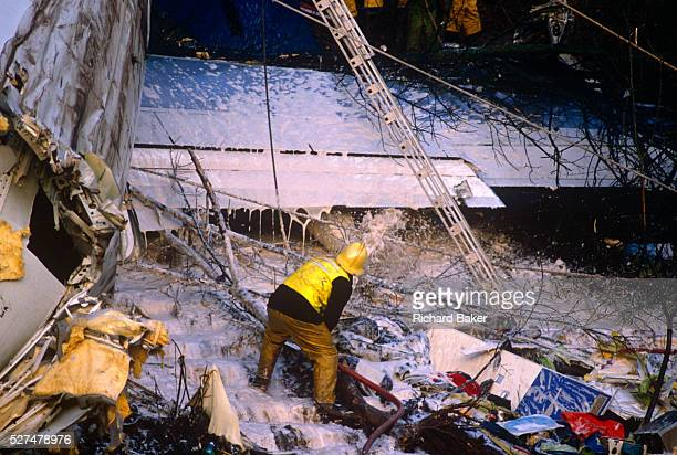 Using ladders and ropes during a rescue operation a fire fighter sprays foam on to the broken fuselage of a British Midland Airways Boeing 737400...