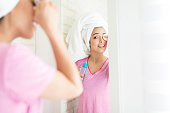 Beautiful woman removing eye makeup while standing in bathroom