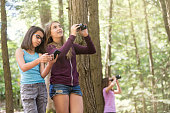 Teen and tween girls exploring nature with binoculars and technology
