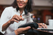 Woman making payment using NFC technology at the shop, cafe or bar