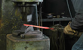 Using pneumatic hammer to shape hot metal. Making the sword out of metal