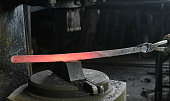 Using pneumatic hammer to shape hot metal. Making the sword out of metal. Side view