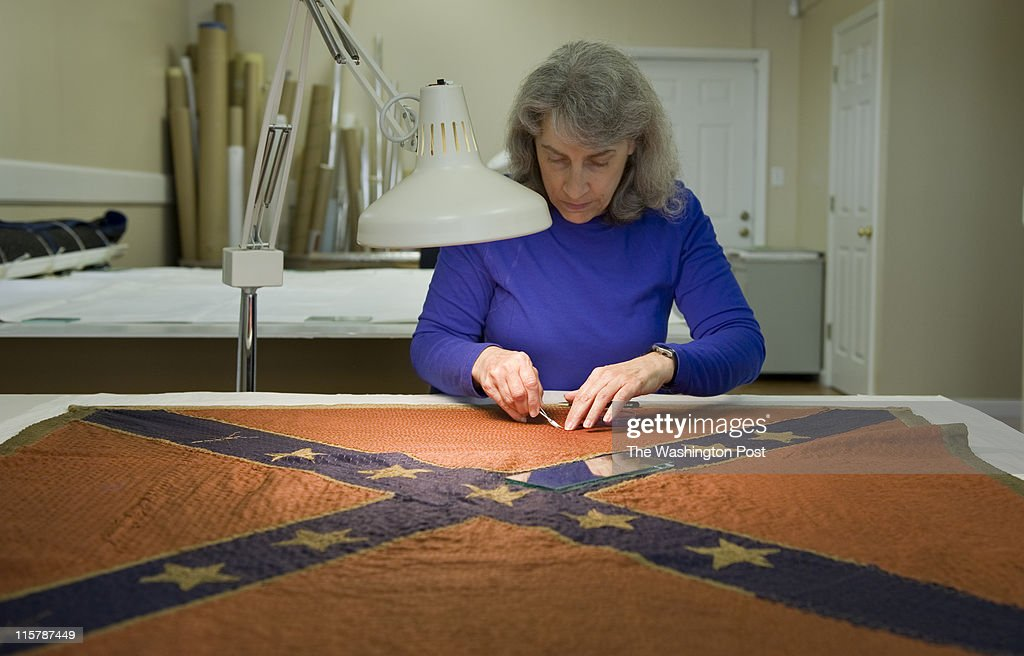 Using scissors and tweezers, Cathy L. Heffner works to restore Civil War era flags, including this '18th VA Flag,' at Textile Preservation Associates Thursday, May, 19, 2011 in Ranson, WV for the Museum of the Confederacy.