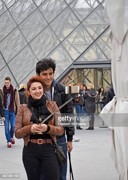Using selfie stick in front of Louvre in Paris France