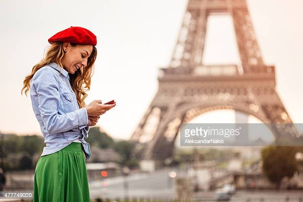 Using smartphone in front of the Eiffel Tower